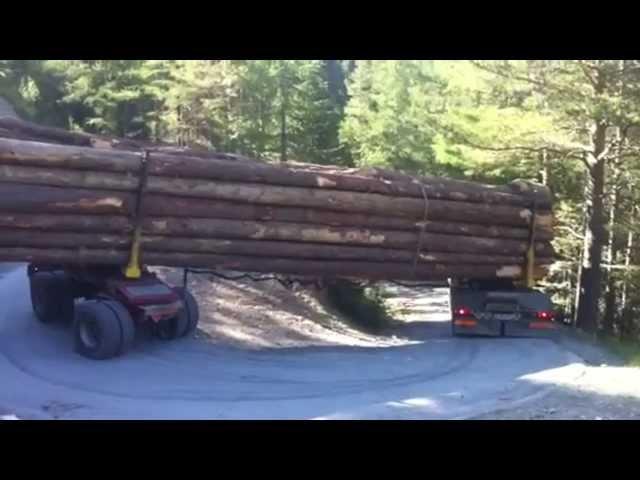 Camion cu busteni executa un viraj pe munte